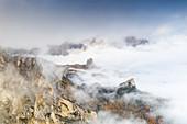 Autumn mist over the larch tree woods surrounding Cinque Torri and Tofane, aerial view, Giau Pass, Dolomites, Belluno, Veneto, Italy