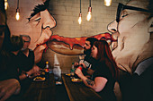 People eating Curry wurst under the famous image of Erich Honecker and Leonid Brezenev kissing each other. Mitte district, BErlin, GErmany