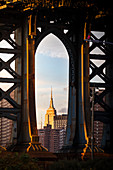 Close up view of the iconic Empire State Building through Manhattan Bridge, from Bumbo district in Brooklin., Manhattan, New York City, USA
