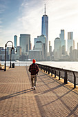 A man admiring Manhattan skyline at sunrise from New Jersey coastline. New York, USA.