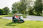 Couple riding on buggy on golf course