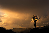 Cyclist lifting bicycle against sunset on hill