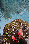 Man's legs in sports shoes standing on rock by stream