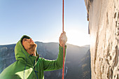 Mountaineer holding onto rope during climb up sheer wall of The Nose, El Capitan, Yosemite National Park.