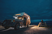 Woman sitting on picnic bench next to camper-van parked near Jordan River, British Columbia, Canada at night.