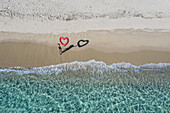 Aerial view of young woman in swimsuit standing on a sandy beach, holding red heart-shaped balloon.