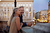 A couple leaning against a balustrade overlooking Vienna during the evening.