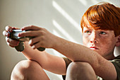 Boy with red hair sitting on floor in sunny room, holding game console controller.