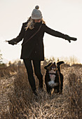 A woman walking with her Bernese mountain dog.