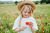 Portrait of young girl holding a poppy, standing in a meadow of wild flowers.