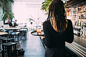 Rear view of waitress wearing black clothes working in bar, carrying drinks on a tray.