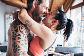 Bearded tattooed man with long brunette hair and woman with long brown hair standing indoors, hugging and kissing.