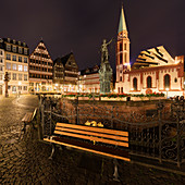 Empty bench on Romerberg in Frankfurt, Germany at night,  during the Corona virus crisis.