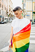 Young lesbian woman standing on a street, wrapped in rainbow flag.