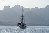Boat in front of the bizarre mountain backdrop of Komodo, Indonesia, Southeast Asia, Asia