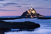 France, Manche, Mont Saint Michel Bay listed as World Heritage by UNESCO, Abbey of Mont Saint Michel illuminated at dusk, Couesnon