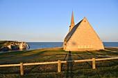 France, Seine Maritime, Pays de Caux, Cote d'Albatre (Alabaster Coast), Etretat, Notre Dame de la Garde chapel, protector of the fishermen, perched on Amont cliff and Aval cliff in the background
