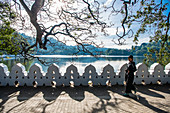 Woman walking around Kandy Lake (Kiri Muhuda or Sea of Milk),artificial lake in heart of hill city,Kandy,Sri Lanka