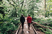 Friends taking walk in forest,Cathedral Grove,British Columbia,Canada