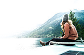 Woman seated on top of campervan overlooking the lake,Cathedral Grove,British Columbia,Canada