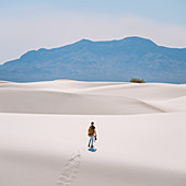 Hiker crossing White Sands National Monument,New Mexico,US