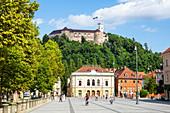 Ljubljana Castle with Slovenian flag behind the Slovenian Philharmonic building, Congress Square, Ljubljana, Slovenia Europe