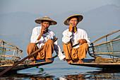 Two Intha leg rowing fishermen smoking cigars, Inle Lake, Shan State, Myanmar (Burma), Asia
