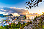 Couple embracing and enjoying the view of Alesund at sunset from Byrampen viewpoint, More og Romsdal county, Norway, Scandinavia, Europe