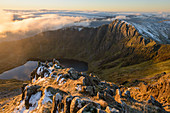 Morning light illuminates the top of Craig Cau during a cloud inversion, photographed from the top of Cadair Idris, Snowdonia, Wales, United Kingdom, Europe