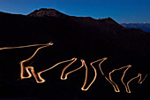 Pass road Stilfser Joch at night with light band of driving cars, long time exposure, South Tyrol, Italy, Europe