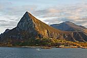 Berglandschaft mit Fischerboot im Schärengarten vor Oernes, Provinz Nordland, Distrikt Salten, Küste von Helgeland, Norwegen, Europa