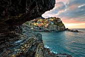 Sunrise on the village of Manarola from a sea cave, Cinque Terre, UNESCO World Heritage Site, Liguria, Italy, Europe