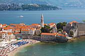 View over crowded beach to the Old Town (Stari Grad), and Budva Bay, Budva, Montenegro, Europe