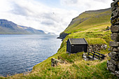 View of a boathouse from Mikladalur to the south to the islands of Kunoy and Bordoy, Mikladalur, Kalsoy, Faroe Islands, Denmark.