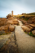 The mean Ruz lighthouse with the red rocks of the Cote de Granit Rose in the foreground, Brittany, France