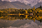 The autumn forest is reflected in the Barmsee, Krün, Bavaria, Germany
