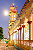 The Cao Dai temple in Vung Tau lit up at dusk with the full moon to the left of the tower, Vung Tau, Vietnam, Indochina, Southeast Asia, Asia