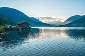 Man on water's edge admiring sunrise over the fjord, Jostedalsbreen National Park, Oppstryn, Sogn og Fjordane county, Norway, Scandinavia, Europe