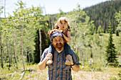 USA, Utah, Uinta National Park, Portrait of smiling man carrying daughter (2-3) on shoulders in landscape