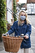 Young blond woman wearing face mask on bicycle with basket, looking at camera.