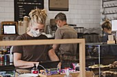 Blond waitress wearing face mask working in a cafe.