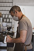 Male barista wearing brown apron and face mask working in a cafe, frothing milk.