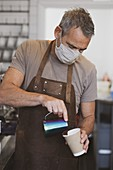 Male barista wearing brown apron and face mask working in a cafe, pouring coffee.