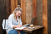 Young blond woman sitting alone at a cafe table with a laptop computer, writing in note book, working remotely.