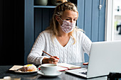 Young blond woman wearing face mask sitting alone at a cafe table with a laptop computer, writing in note book, working remotely.