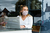 Young blond woman wearing face mask sitting alone at a cafe table with a laptop, working remotely.