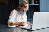 Woman wearing face mask sitting alone at a cafe table with a laptop , writing in note book, working remotely.