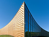 Modern university buildings, wooden beams projecting from a curved wood cladding wall, on a curved ground surface
