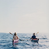Middle aged man and woman sea kayaking at dusk
