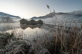 Three fishing huts on the Kochelsee in the morning light near Schlehdorf, Bavaria, Germany.